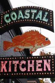 Coastal Kitchen's original sign still calls attention to the Capitol Hill restaurant, which opened in 1993.
