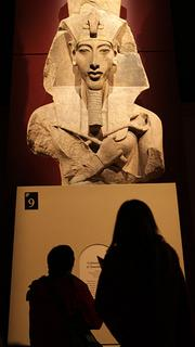 """Visitors look up at a colossal statue of Amenhotep IV on display at """"Tutankhamun: The Golden King and the Great Pharaohs"""" at the Pacific Science Center."""