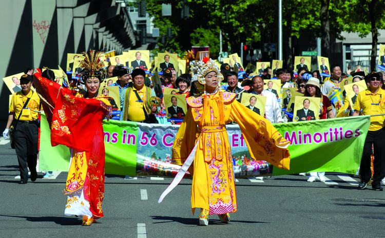 """A group of Lions Club members from China walk south on 5th Avenue at the beginning of today's parade. Their banner says, """"Fashions in 56 Chinese Ethnic Minorities."""" The Lions Club International convention is one of the biggest ever in Seattle."""