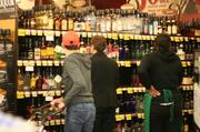 Customers eye liquor prices on the shelves at a West Seattle QFC. Some were taking notes for comparison with other stores. Many were complaining about taxes that would be added at checkout.