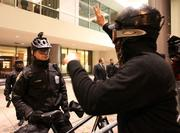 A masked protester screams at a Seattle Police Department bicycle officer protecting the downtown Seattle Sheraton where Jamie Dimon, chairman and CEO of JPMorgan Chase & Co. was delivering a speech on Wednesday.