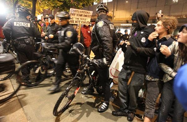 Seattle Police Department bicycle officers break through a perimeter of several hundred Occupy Seattle protesters surrounding the downtown Seattle Sheraton where Jamie Dimon, chairman and CEO of JP Morgan Chase & Co., was delivering a speech on Wednesday.