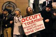 Occupy Seattle protesters chant and lock arms to surround the downtown Seattle Sheraton where Jamie Dimon, chairman and CEO of JP Morgan Chase & Co., was delivering a speech on Wednesday.
