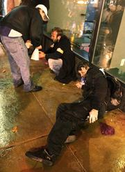 Two protesters who collapsed to the ground get help from a passerby after they were pepper sprayed by Seattle police at a demonstration at the downtown Seattle Sheraton where Jamie Dimon, chairman and CEO of JP Morgan Chase & Co., was delivering a speech on  Wednesday.