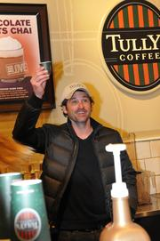 Actor Patrick Dempsey raises a cup at a Tully's coffee shop in Bellevue's Lincoln Square.
