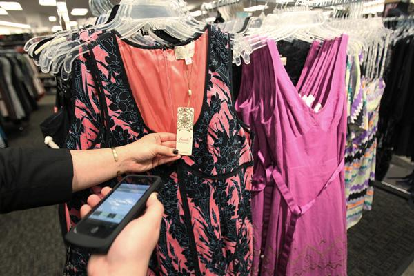 A shopper scans the price tag of a dress at Nordstrom Rack. The parent company reported a 9.8 percent increase in same-store sales.