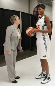Shannon Burley, left, vice president of marketing for the Seattle Storm, chats with 6-foot-4-inch Ashley Robinson.