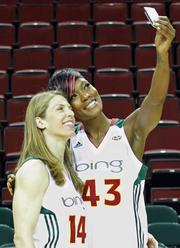 The Seattle Storm players Katie Smith, left, and Ashley Robinson take their own photo during a break.