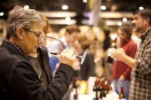 Andrew Will Winery owner Chris Camarda sips wine at Taste Washington while winemaker Mark McNeilly chats with consumers.