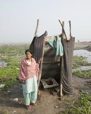 A woman stands beside a makeshift toilet in a slum colony on the bank of the Yamuna River in New Delhi, India.