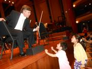 Before the opening night concert of Seattle Symphony  a brother and sister rushed to the stage to reach up to Second Assistant Concert Master Simon James. Sophie, 8, is one of James's violin students. Her brother, Benjamin, 5, says he wants to play violin too.
