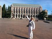 "At University of Washington's Red Square in late August, Kerry Payne (my sister-in-law), points to a banner that indicates ""Real Dawgs wear purple on Fridays."" Payne toured the campus as part of her wish list of things to do while she was here."