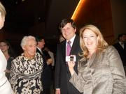 Seattle Symphony supporter Jane Davis, left, with philanthropist Charles Simonyi, middle, and Jody Schwarz, wife of Gerard Schwarz, right. Jody Schwarz is holding Simonyi's smartphone with a picture of Charles and Lisa Simonyi's 5-month-old baby.