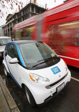 A Car2Go Smart Car sits parked on Westlake Avenue North in Seattle while a red-colored South Lake Union Transit car blurs past.