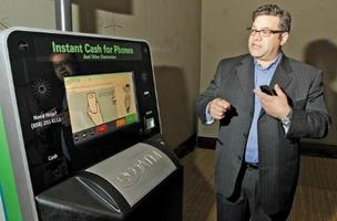 EcoATM CEO Tom Tullie demonstrates the EcoATM, a Coinstar kiosk that offers cash for old cell phones.