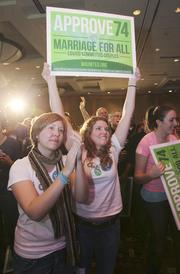 Referendum 74 supporters Laura Gentry (left) and Carollani Sandberg cheer as results are announced that the same-sex marriage referendum leads in the polls by 52% during election night festivities at the Westin Hotel in Seattle, November 6, 2012.