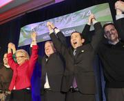 Referendum 74 supporters Governor Christine Gregoire (left, red), State Senator Ed Murray (center) and Michael Shiozaki (second right) and Eric Pederson (right) cheer on stage as polls show that referendum shows a 52 percent  lead in the polls during election night festivities at the Westin Hotel in Seattle, November 6, 2012.