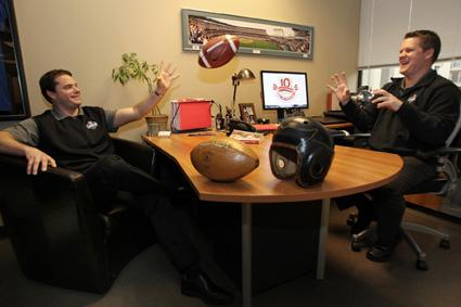 PASSING PLAY: Explore Consulting partners Steve Jones, CEO (left) and Jeremy DeSpain, COO toss a football in their Bellevue offices.