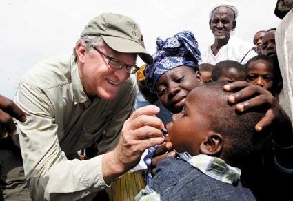 Jeff Raikes in 2011 administers polio drops to a Nigerian child during an African trip that focused on ending polio and building other immunization programs. Raikes' rural upbringing often helps him connect with the recipients of Gates Foundation programs.