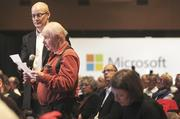 Microsoft Shareholder Don Shuper (in red) speaks to the senior executives Steve Ballmer, Bill Gates and Brad Smith (all unpictured) on stage about the cumulative vote proposal by shareholders during the the annual Microsoft shareholders meeting.