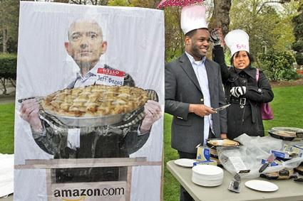 "Ken Taylor, with Working Washington, and Heather Villanueva, with Service Employees International Union Healthcare 775NW, serve up slices of pie at an April 17 ""occu-pie"" protest at Seattle's Denny Park. Demonstrators later marched to Amazon's headquarters to call attention to the company's rate of corporate tax."