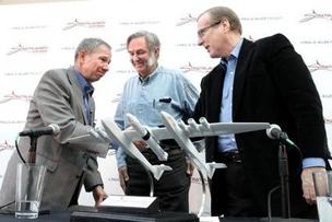 Stratolaunch Systems board members Mike Griffin, former NASA administrator, and Burt Rutan, areospace designer, shake hands with Paul Allen at a press conference for Stratolaunch Systems. A model of the carrier aircraft with multi-stage rocket booster and human space capsule is in the foreground.