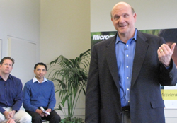 Microsoft CEO Steve Ballmer speaks at Microsoft's 'Citizenship Accelerator Summit' with employees Tom Moran and Rajesh Munshi behind him.