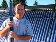 Our Lady of the Lake principal Vince McGovern holding a solar tube on the roof of the school.