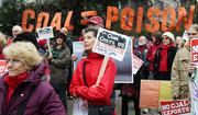 Anti-coal protestors Paula Rotondi (center in red) of Birch Bay attends a demonstration at Jim Ellis Freeway Park next to the Washington State Convention Center in Seattle  on Thursday.