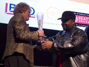 Terri Boehm of Group Health Cooperative, left, accepts the award for Mobile App of the Year from Sir-Mix-A-Lot at the TechFlash Newsmaker Awards. Group Health Mobile, a smartphone app for patients, was co-developed with Slalom Consulting.