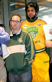 """Seattle Sonics fans Brian Robinson, left, president of ArendaSolution.org, and Kris """"Sonics Guy"""" Brannon listen to a press conference by Seattle City Council President Sally Clark and council members Mike O'Brien and Tim Burgess at City Hall announcing a proposed new agreement with Chris Hansen's ArenaCo for a new arena to be built with the hopes of bringing an NBA team back to Seattle."""