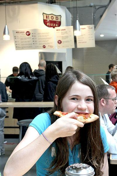 Elizabeth Hert takes a bite at Mod Pizza at the Armory/ Center House at Seattle Center for. Mod Pizza is one of a number of new food options at the Armory.