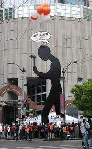 """Protesters from the Backbone Campaign used giant helium balloons to suspend this """"thought bubble"""" over the Hammering Man during demonstrations at the Amazon.com shareholders meeting at the Seattle Art Museum on Thursday."""