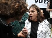 """Emergency room registered nurse Patrice Ruhl (right) yells """"get a job"""" at a protester (left) who grabbed her by the wrist when Ruhl stood up to protest against the more than 200 demonstrators outside the Amazon.com shareholders meeting at the Seattle Art Museum on Thursday"""