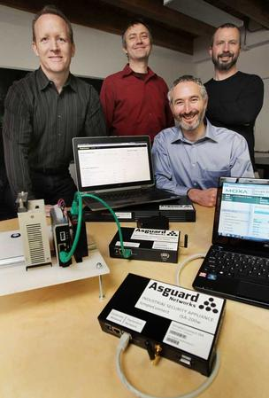 David Mattes (bottom right), founder of Asguard, displays some of the  company's industrial security systems. He's joined by colleagues (top, left to right) Curtis Vredenburg, Ludwin Fuchs and Eric Artzt at their office in Seattle's Fremont district.