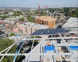 Solar roof of the Bullitt Center under construction. The 242-kilowatt photovoltaic array will provide as much electricity as the building uses in a year. Tenants will be allocated an energy budget based on the percentage of the building they occupy. If they remain within their budget, tenants will pay nothing for electricity.