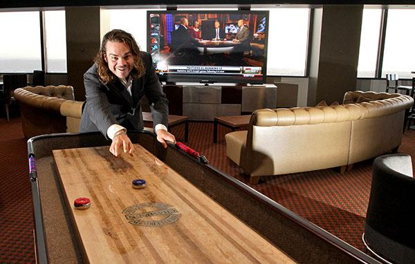 Tommy Trause, general manager of the Columbia Tower Club, tries out the new shuffleboard table that's part of the club's $3.5 million renovation, which also includes the 103-inch TV in the background.