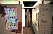 Brett Cameron, general manager of Star Studio, demonstrates Coinstar's new advanced photo booth. Star Studio is being tested at several malls in the Los Angeles area. Customers can choose different scenarios and backgrounds for their photos.