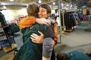 Sally Jewell and Joe Weczorek, an employee at REI's Seattle store, share a hug.