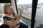 Former Seattle City  Councilwoman Jan Drago uses an iPad to photograph and film her first ride