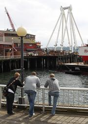 Seattle waterfront visitors watch construction on the Seattle Great Wheel on Pier 57 on May 9.