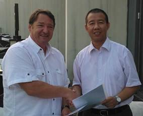 Greenpoint Chairman Jon Buccola, left, and Ameco Beijing General Manager Hu Yuilang shake hands over their deal.