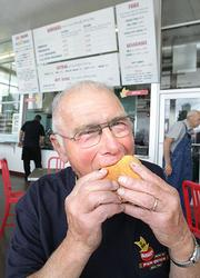 Joe Burgi, whose family owns the original Pick-Quick Drive In in Fife and is a partner in the Pick-Quick Drive In in Auburn (pictured here) bites into a classic burger.