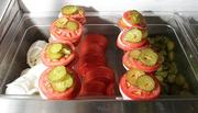 Fresh sliced tomato, fresh sliced onion and pickles wait to be placed on made-to-order burgers at the Pick-Quick Drive In in Auburn