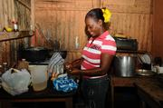 Brigida Rodriguez prepares food in her kitchen to sell in her town in the Dominican Republic.