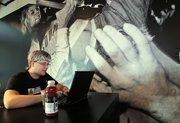 "Michael VanBummel, a Google software engineer, works under a photo of Nirvana rocker Kurt Cobain in the ""grunge"" office lounge at Google in Kirkland."