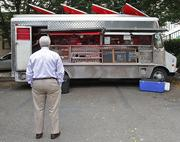 An office worker from South Lake Union near the Amazon campus waits to order some Caribbean food from the Jerk Station food truck.
