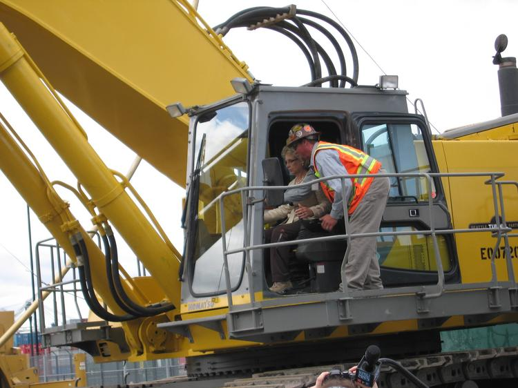 Gov. Chris Gregoire operates the backhoe that lifts the first load of dirt at a ceremony celebrating the beginning of work on Seattle's deep-bore tunnel.