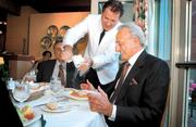 Il Terrazzo Carmine waiter Walter Vianello grates cheese on Michael R. Mastro's pasta.