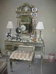 Mirrored vanity with two glass lamps, etched mirror and stool.